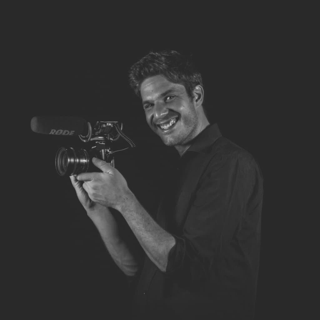 Daniel Zapata sonriendo sujetando una cámara