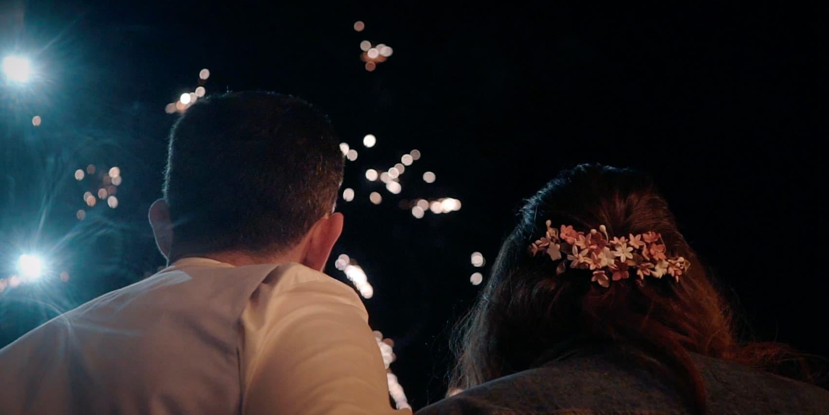 Dos personas recién casadas mirando los fuegos artificiales por al noche