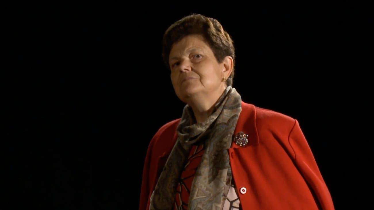 Señora mayor con chaqueta roja mirando desafiadamente